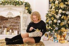 甜妇女微笑并且摆在坐圣诞节背景  免版税库存图片