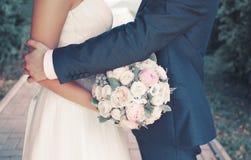 甜婚礼加上牡丹柔和的花束开花,拥抱可爱的新娘的肉欲的新郎 免版税库存照片