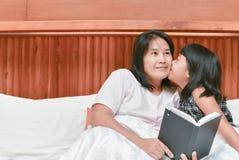 甜小女孩亲吻她的面颊的妈妈 库存图片
