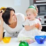 甜小女孩和母亲获得乐趣在厨房 库存照片