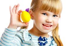 甜小女孩用黄色复活节彩蛋 免版税库存图片
