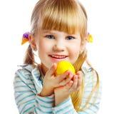 甜小女孩用黄色复活节彩蛋 免版税图库摄影