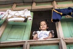 甜小女孩从她的与垂悬的衣裳的木房子窗口在顶端凝视下来 库存图片
