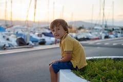 甜小孩,小孩男孩,坐和观看港口 免版税库存图片