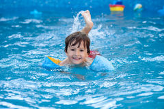 甜小男孩,游泳在大游泳池 免版税库存图片