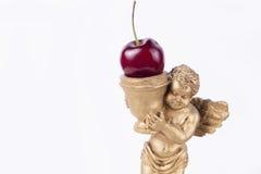 甜小的金子天使雕象用樱桃(白色演播室背景) 免版税图库摄影