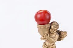 甜小的金子天使雕象用西红柿(白色演播室背景) 免版税库存图片