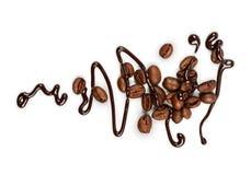 甜巧克力调味汁和咖啡豆在白色 库存照片