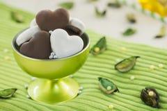 甜布朗和白色蜂蜜心脏在绿色玻璃 库存照片