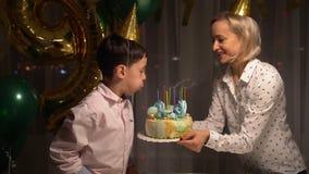 甜快乐的小孩男孩的中央部位,在蛋糕的吹的蜡烛和在他的生日聚会期间的拍的手在家 股票视频