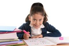 甜愉快的拉丁孩子坐做家庭作业和微笑的书桌 库存图片