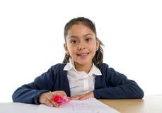 甜愉快的拉丁孩子坐做家庭作业和微笑的书桌 免版税库存照片