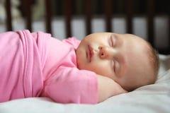 甜新出生的女婴睡着在小儿床 免版税库存照片