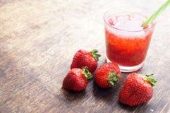 甜新鲜的草莓汁,在木桌,选择聚焦上的圆滑的人 库存照片