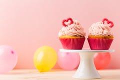 甜杯形蛋糕和气球在安排 免版税库存照片