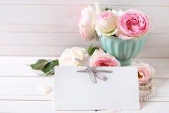 甜桃红色玫瑰在花瓶和空标识符开花在被绘的白色 免版税库存照片