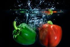 甜椒下落到在黑背景的水里。 免版税库存图片