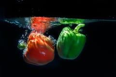 甜椒下落到在黑背景的水里。 免版税图库摄影