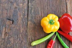 甜椒在木桌上的黄绿色红色 库存图片
