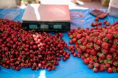 甜樱桃和草莓在一个农厂市场上在城市 水果和蔬菜在农夫夏天市场上 樱桃 免版税库存图片