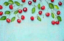 甜樱桃边界在分支的与绿色在浅兰的背景,顶视图,文本的地方离开 免版税库存图片