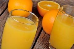 甜橙结果实用在一块玻璃的汁液在桌上 库存照片