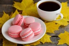 甜法国蛋白杏仁饼干 在一块白色板材,一杯咖啡的浅粉红色的蛋白杏仁饼干,黄色在老木背景离开 免版税图库摄影