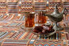 甜点、日期和茶在地毯 免版税库存照片
