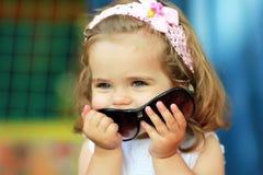 甜点一个岁女孩` s被窃取的妈妈` s太阳镜和愉快佩带他们设法看起来长大 免版税库存照片