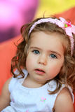 甜点反对被弄脏的明亮的五颜六色的背景的一个岁女孩 免版税库存照片