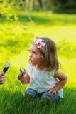 甜点吃冰淇凌的一个岁女孩坐草坪在夏天 库存照片