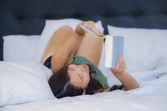 甜点和相当年轻亚洲妇女或少年读书新颖的书在床或学习上放松的在家说谎在床卧室comfo的 图库摄影