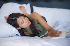 甜点和相当年轻亚洲妇女或少年读书新颖的书在床或学习上放松的在家说谎在床卧室comfo的 免版税库存图片