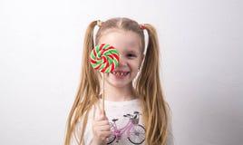 甜点和童年:女孩是一个少年用花糖果和 库存图片