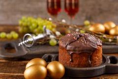 甜点和葡萄在欢乐桌上 复活节金黄蛋糕和朱古力蛋 对待在木背景的一个假日 复活节 免版税库存照片