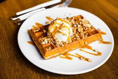 甜点心的食品组成 与白色冰淇凌的比利时华夫饼干装饰用焦糖和坚果 免版税库存照片