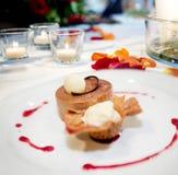 甜点心盘、浪漫餐馆桌准备好与冰淇凌和曲奇饼 图库摄影