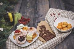 甜点特写镜头在一块白色板材的:椰子饼干,pastila,蛋白甜饼,奶油玫瑰,土耳其快乐糖,在残破的巧克力旁边 免版税库存图片
