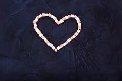 甜点黑背景的标志心脏 顶视图 免版税库存照片
