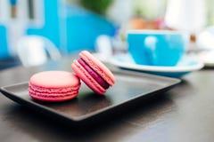 甜点,新macarons用在一个蓝色杯子的咖啡在一张黑桌上 免版税库存图片