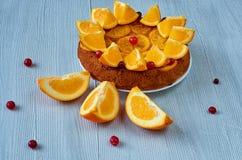 甜焦糖的橙色饼装饰用红色蔓越桔和新橙色切片在灰色背景 柑橘饼 库存照片