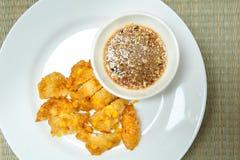 甜玉米油炸馅饼,在一块白色板材的酥脆油煎的玉米在竹子 免版税库存照片