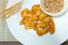 甜玉米油炸馅饼,在一块白色板材的酥脆油煎的玉米在竹子 免版税库存图片