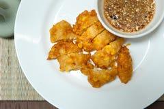 甜玉米油炸馅饼,在一块白色板材的酥脆油煎的玉米在竹子 图库摄影