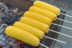 甜玉米烤了在火炉的烧伤在市场摊位 免版税库存图片