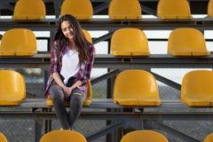 甜甜地坐在立场和微笑的孤独的啦啦队员女孩 免版税库存照片