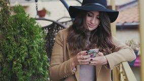 甜甜地穿一个黑经典帽子和一件米黄外套,微笑的特写镜头年轻浅黑肤色的男人,读在她的智能手机的sms 慢 股票录像