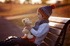甜男孩,坐与女用连杉衬裤的长凳涉及日落 库存照片