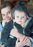 甜男婴在温暖的冬天穿衣与母亲 免版税库存照片