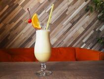 甜白色和黄色鸡尾酒与牛奶泡沫和与桔子和樱桃片断  库存图片